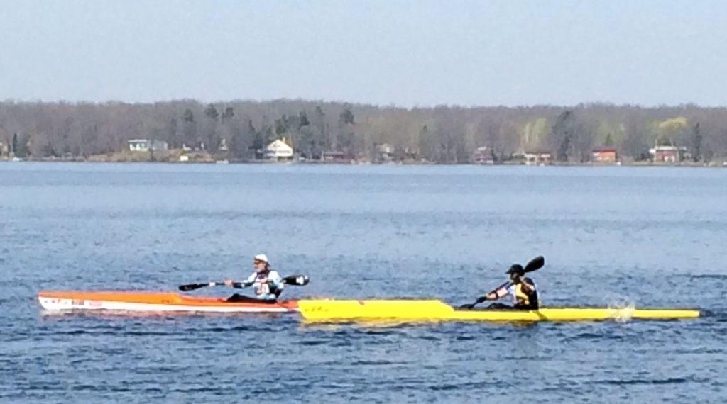 2 people paddling in kayaks.