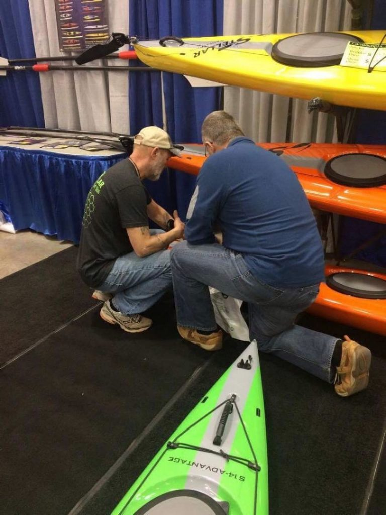 Joe Zellner showing customer an orange Stellar Kayak.