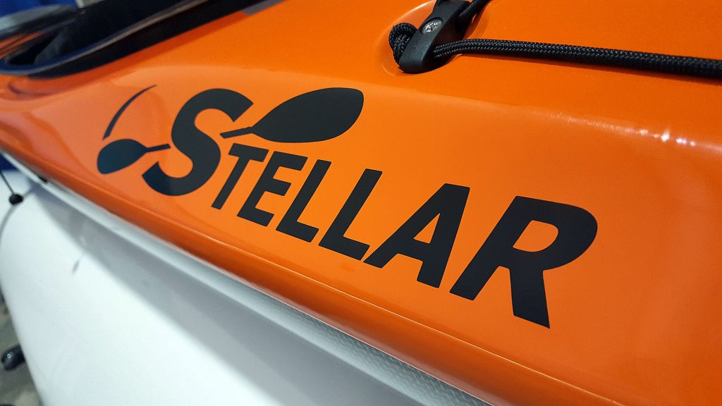 A close up of an orange Stellar Kayak with vinyl logo on a rack at Canoecopia.