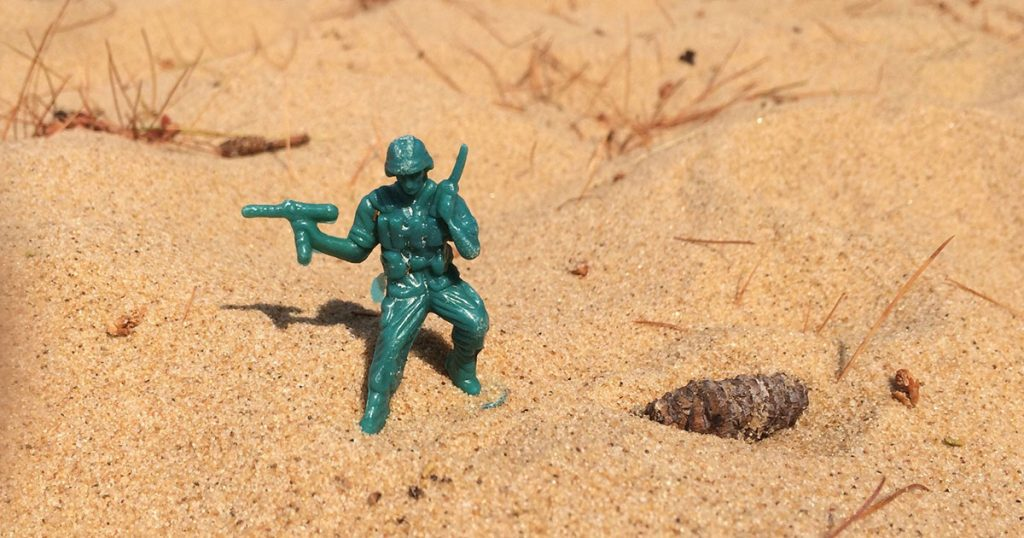 Little green Army Man on a sandy beach.