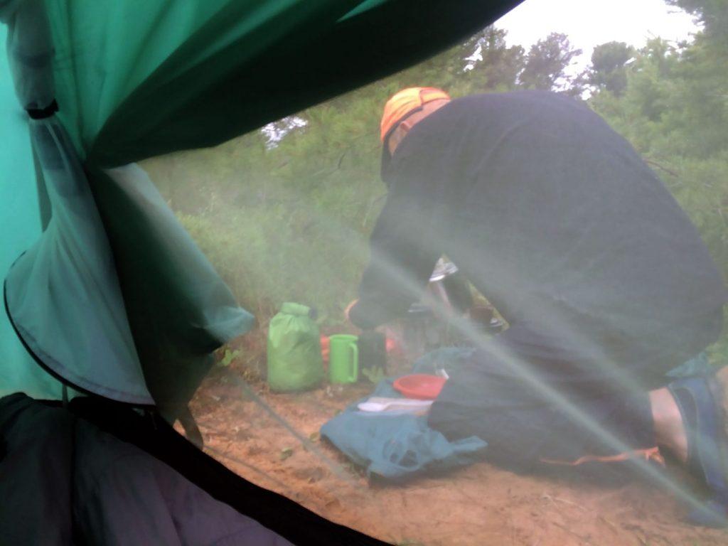 Joe making coffee outside tent.