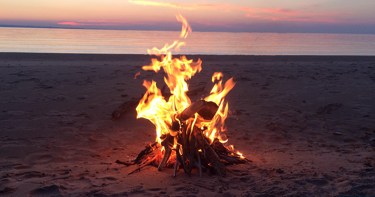 Lake Superior sunset with a campfire on the beach.